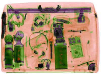 Imagem gerada por uma máquina de raios X (Observe que todos os objetos orgânicos estão representados em uma coloração alaranjada e os inorgânicos em verde; imagem cedida por L-3 Communications)