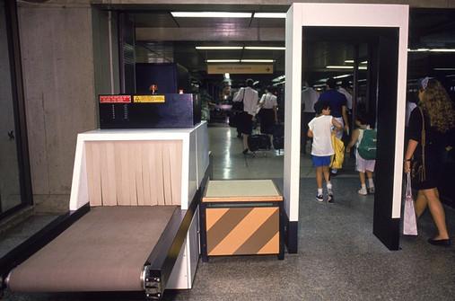 Máquina de raios X (esquerda) para a bagagem de mão e detector de metais (portal à direita) para os passageiros