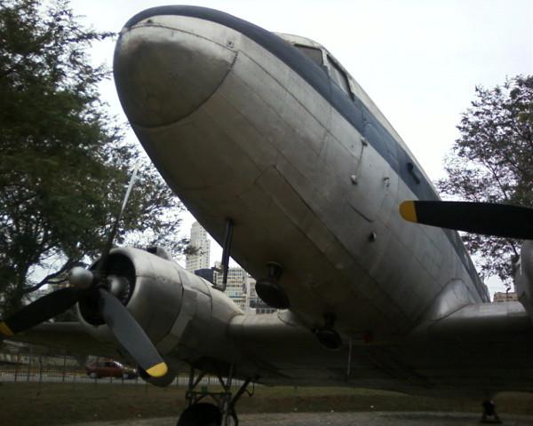 Avião DC-3 da VASP, antes utilizado na 2ª Guerra Mundial e agora em exposição no espaço Catavento (Parque Dom Pedro, centro de São Paulo - note o Ed. Altino Arantes no vão)
