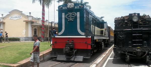 Estação Jaguariúna da VFCJ com locomotiva a diesel e composição com Maria Fumaça e carro contendo madeira para queima sobre trilhos instalados em calçado e asfalto. Foto: ViniRoger.