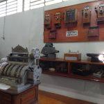 Telefones antigo, caixa registradora e outros itens