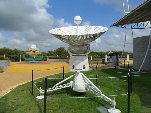 Antena para rastreamento de sondas meteorológicas. Ao fundo à esquerda está uma estação de rastreio de satélite Baker-Nunn e à direita estão o lançador original e a réplica do foguete Nike-Apache. Foto: ViniRoger