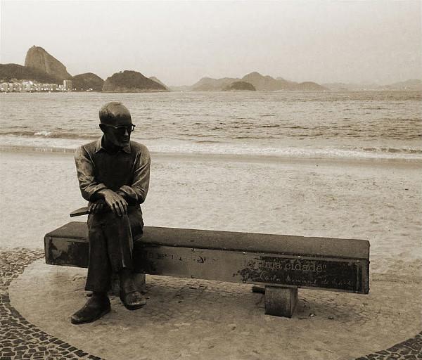 """Estátua de Drummond na Praia de Copacabana - """"No mar estava escrita uma cidade"""". Fonte: Wikipedia"""