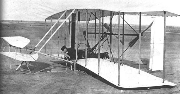 Flyer 1 e Wilbur Wright em 14 de dezembro de 1903 - profundor ficava à frente do avião. Fonte: Wright-Brothers.org