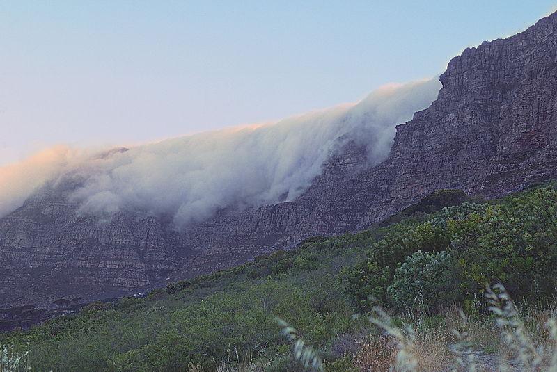 """Formação de nuvens """"toalha de mesa"""" sobre a face norte da Table Mountain (câmera apontada para Leste-Sudeste). Foto: KodachromeFan/Wikipedia, CC BY-SA 3.0"""